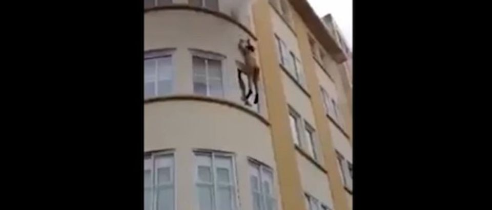 Half-naked woman falls from burning apartment in video