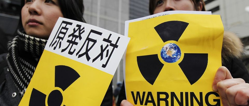 """Anti-nuclear protester hold signs in front of Tokyo Electric Power Co.'s (TEPCO) headquarters in Tokyo April 3, 2011. Japanese engineers grappling on Sunday to end the world's worst nuclear crisis since Chernobyl tried to seal a crack that has been leaking radiation into the ocean from a reactor crippled by a massive earthquake and tsunami. The sign (L) reads in Japanese,""""Anti-nuclear"""". REUTERS/Yuriko Nakao"""
