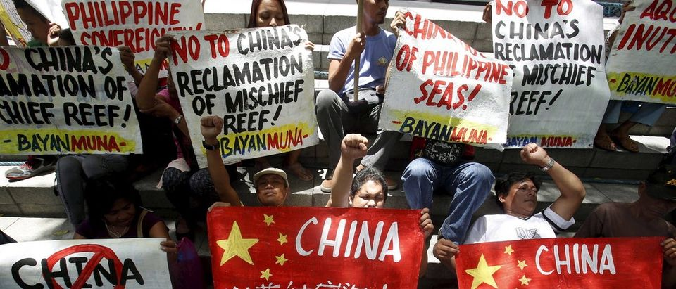 Members of Bayan Muna (Country First) Party List group display placards during a picket rally over territorial dispute with China in South China Sea, outside the Chinese Consulate in Makati