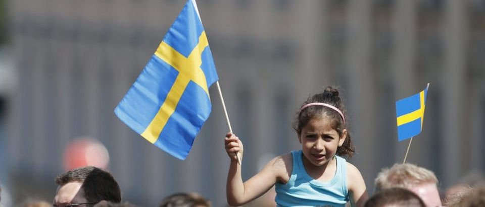 A girl waves flags outside the royal church where the Swedish royal wedding will take place, in Stockholm