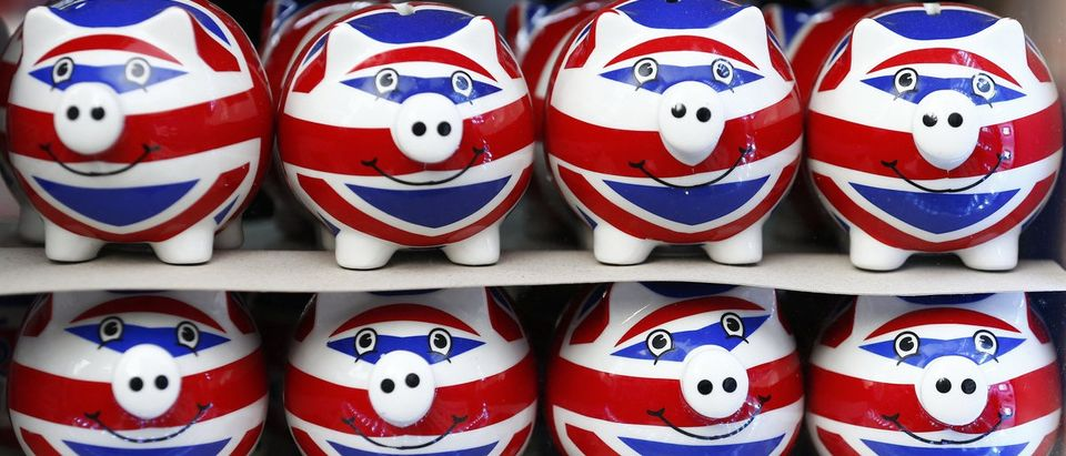 Smiling Union Jack piggy banks are lined up for sale in the window of a souvenir store on Oxford Street in central London