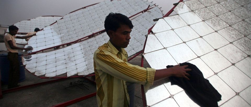 Workers clean solar concentrator panels at Kapodra village