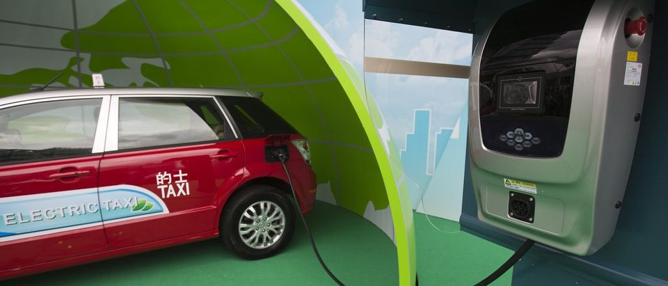 A BYD E6 electric car, which will be used as a taxi, is seen plugged into a charging unit during a launch ceremony for the line vehicles in Hong Kong