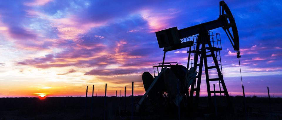 Operating oil and gas well profiled on sunset sky Calin Tatu/Shutterstock.com