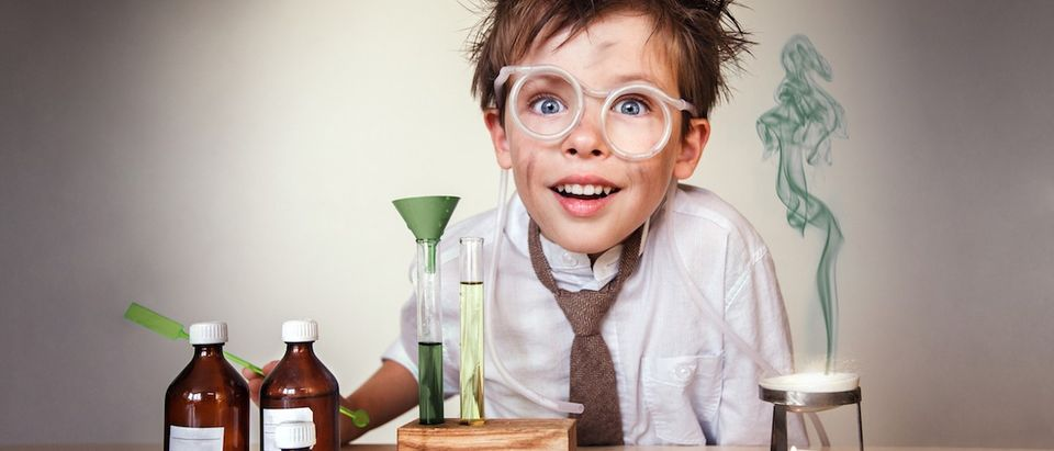Crazy scientist. Young boy performing experiments. (Shutterstock)
