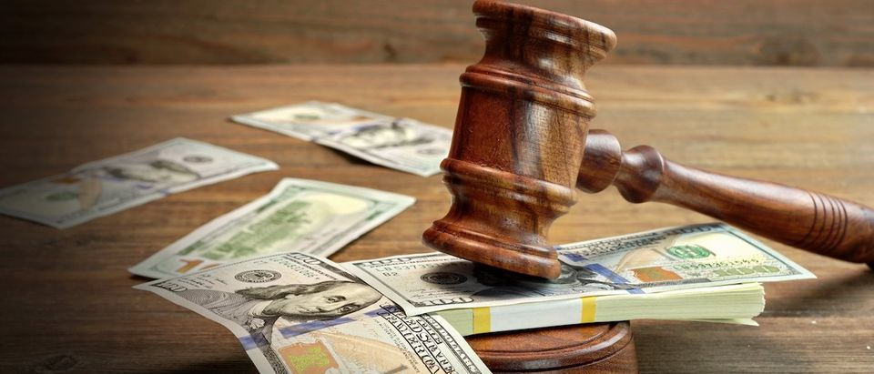 A gavel rests atop a wad of $100 bills.