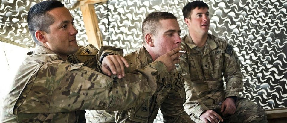 US soldiers share a cigarette at Command Outpost AJK in Maiwand District, Kandahar Province, Afghanistan
