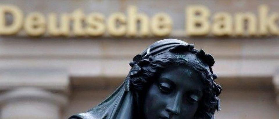 A statue is seen next to the logo of Germany's Deutsche Bank in Frankfurt