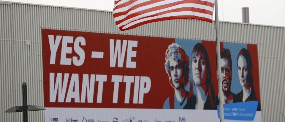 The flag of the USA flutters over a hall of the Hanover Fair decorated with a banner supporting the free trade agreement TTIP in Hanover