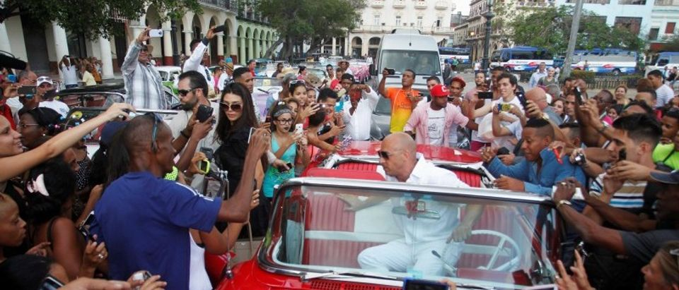 Actor Vin Diesel climbs out of a vintage car while surrounded by fans, as he arrives to attend a fashion show by Chanel, the first major fashion house to send models down the catwalk in Cuba, in Havana