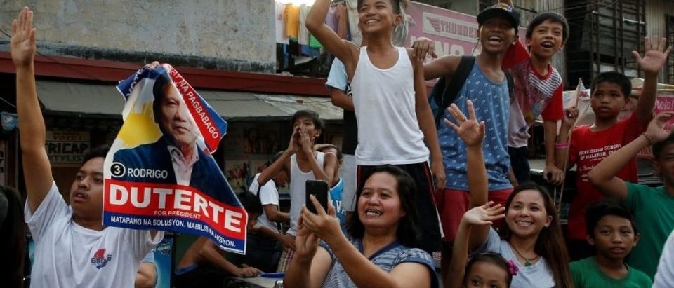 """Supporters watch the motorcade of presidential candidate Rodrigo """"Digong"""" Duterte during election campaigning in Malabon, Metro Manila"""