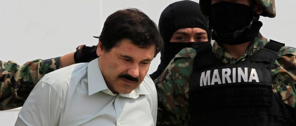 """Joaquin """"El Chapo"""" Guzman (L) is escorted by soldiers during a presentation at the Navy's airstrip in Mexico City"""