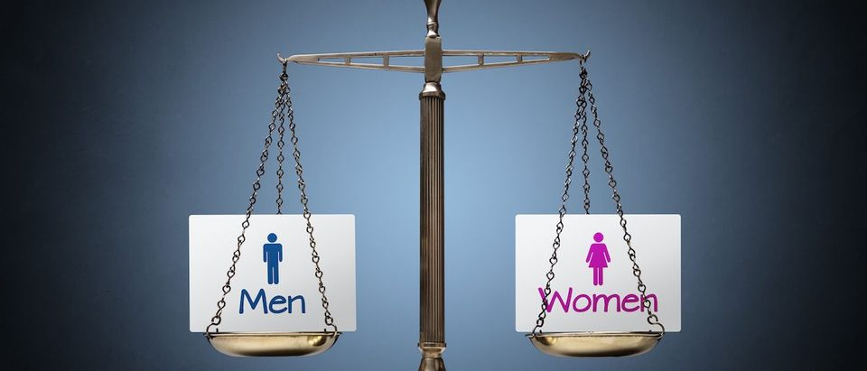 Equality between man and woman concept with beam scales and sign Shutterstock