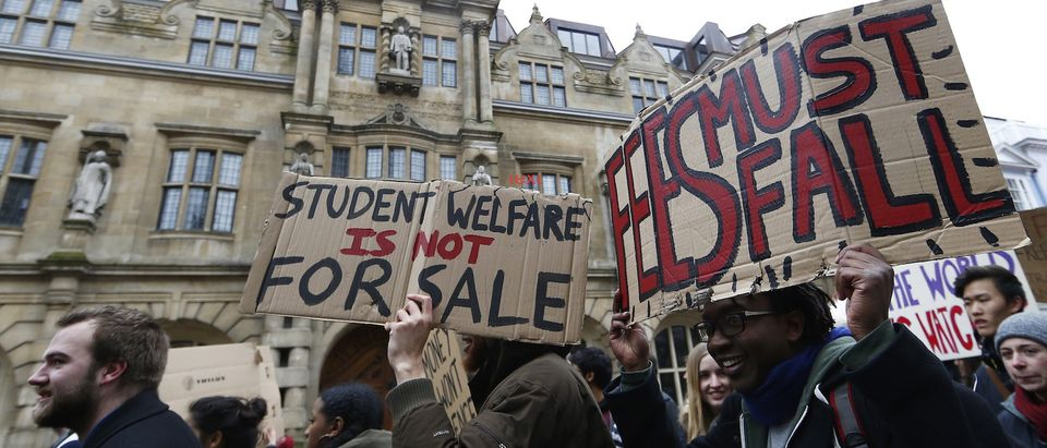 Students protest under the statue of Cecil Rhodes outside Oriel College in Oxford University