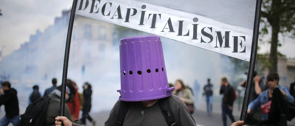 A protester wears a garbage can during a demonstration against French labour law in Nantes