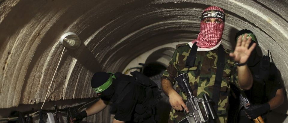 File photo shows a Palestinian fighter from the Izz el-Deen al-Qassam Brigades, the armed wing of the Hamas movement, gesturing inside an underground tunnel in Gaza