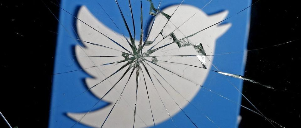 A 3D-printed Twitter logo is seen through broken glass, in this picture illustration taken