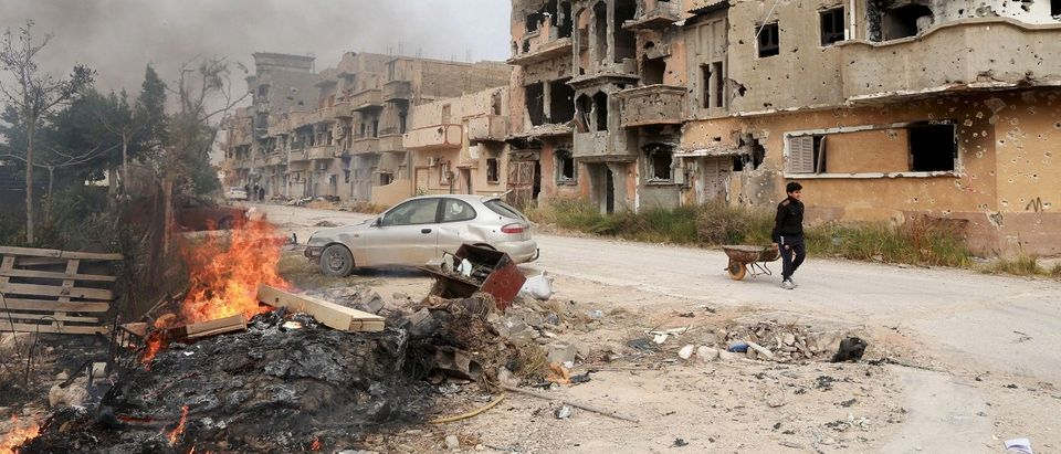 A man pulls a wheelbarrow past destroyed buildings after clashes between military forces loyal to Libya's eastern government and Islamist fighters, in Benghazi