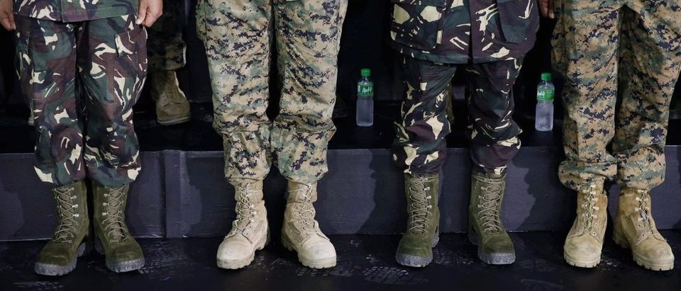 The various boots worn by multi-nation troops are seen as the soldiers listen to President Barack Obama speak to military troops at the Fort Bonifacio Gymnasium in Manila, April 29, 2014