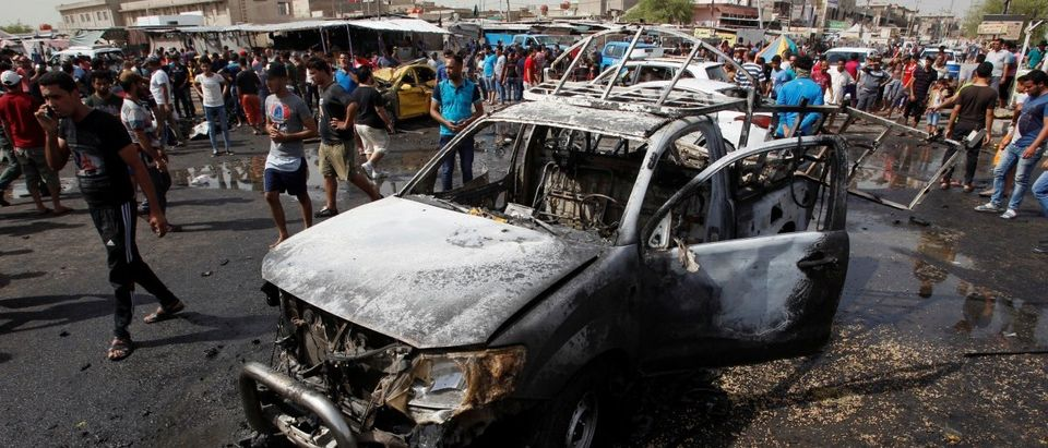 People gather at the site of a car bomb attack in Baghdad