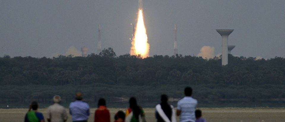 People watch as India's GSLV-D6 blasts off carrying a 2117 kg GSAT-6 communication satellite from the Satish Dhawan space centre at Sriharikota