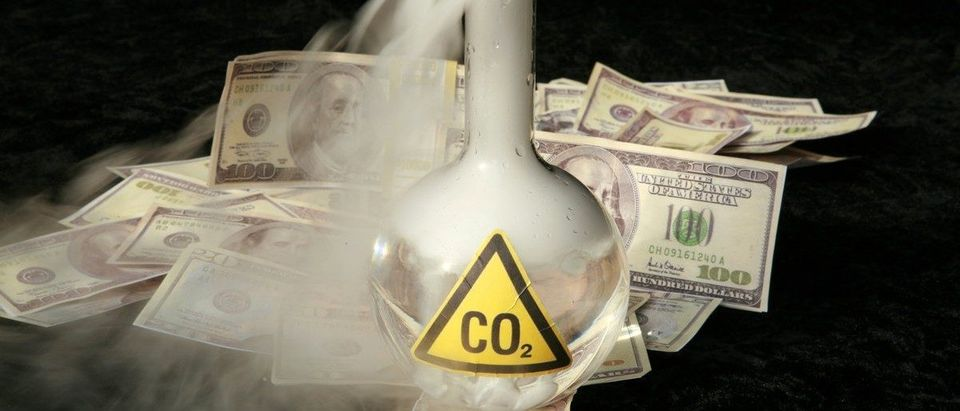 A 500ml beaker filled with CO2 infront of a pile of money, representing the business interest behind the Global Warming scare Shutterstock.com / mikeledray