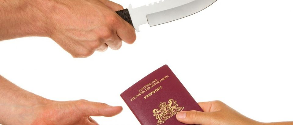Man with knife threatening a woman to give her Dutch passport. (Credit: MyImages - Micha / Shutterstock.com)