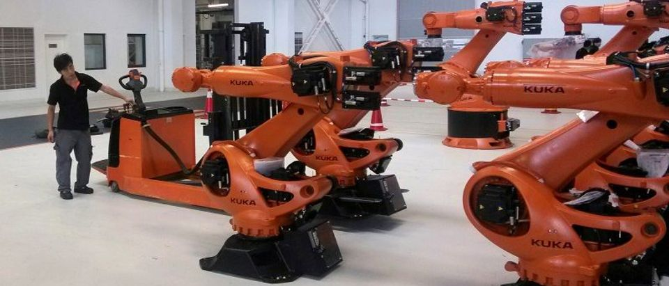 A staff member stands next to robots at a plant of Kuka Robotics in Shanghai
