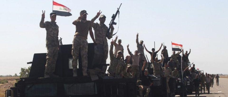 Iraqi security forces members gesture near Falluja, Iraq