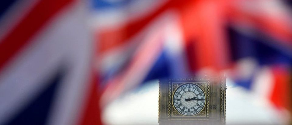 British Union flags fly in front of the Big Ben clocktower of The Houses of Parliament in central London