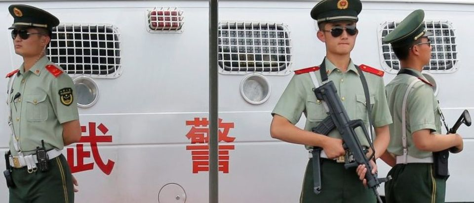 Paramilitary policemen hold weapons as they provide security near Tiananmen Square in Beijing