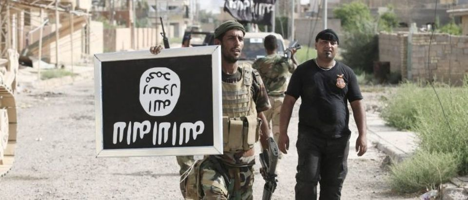 Shi'ite fighters hold an image of the Islamic State flag after clashes with IS militants in Saqlawiya