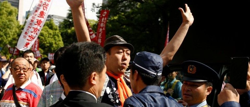 A right-wing protester confronts a participant of a rally against the policies of Japanese Prime Minister Shinzo Abe in Tokyo