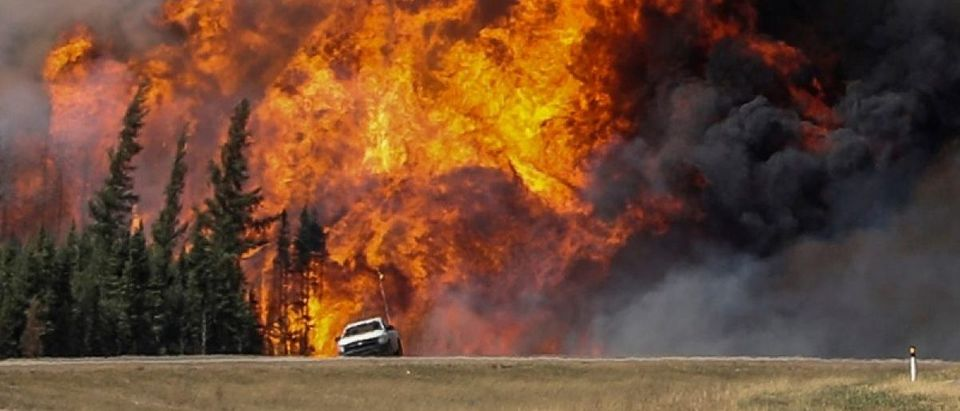 Smoke and flames from the wildfires erupt behind a car on the highway near Fort McMurray