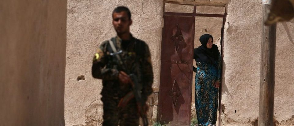 A Syria Democratic Forces (SDF) fighter stands near a woman looking out a doorway in a village, on the outskirts of Manbij city, after they took control of it from Islamic State forces