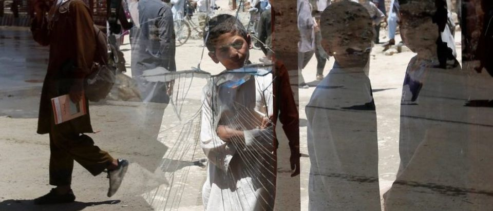 Afghan boys look a damaged window of a shop after a suicide attack in west of Kabul, Afghanistan