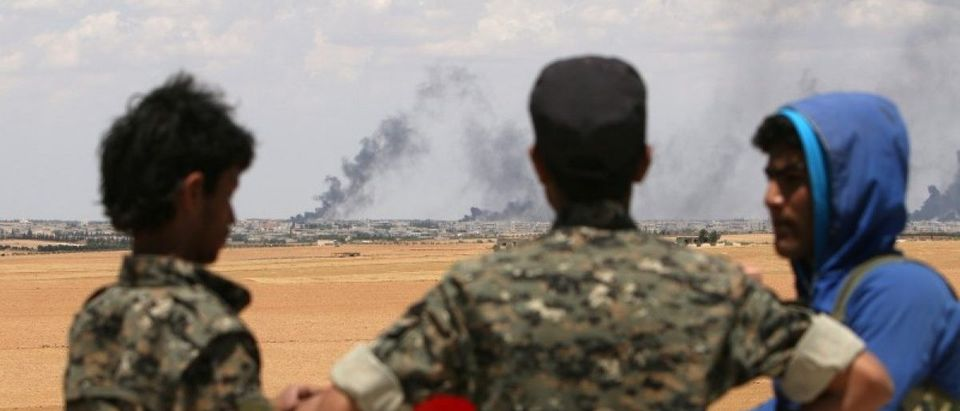 Manbij Military Council fighters stand at a checkout point overlooking rising smoke from Manbij city, Aleppo province, Syria