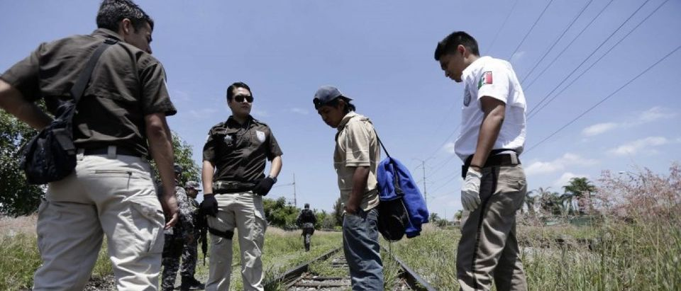 Mexican immigration officers talk with a man whom they suspect to be an illegal immigrant during a search operation in Zapopan near Guadalajara