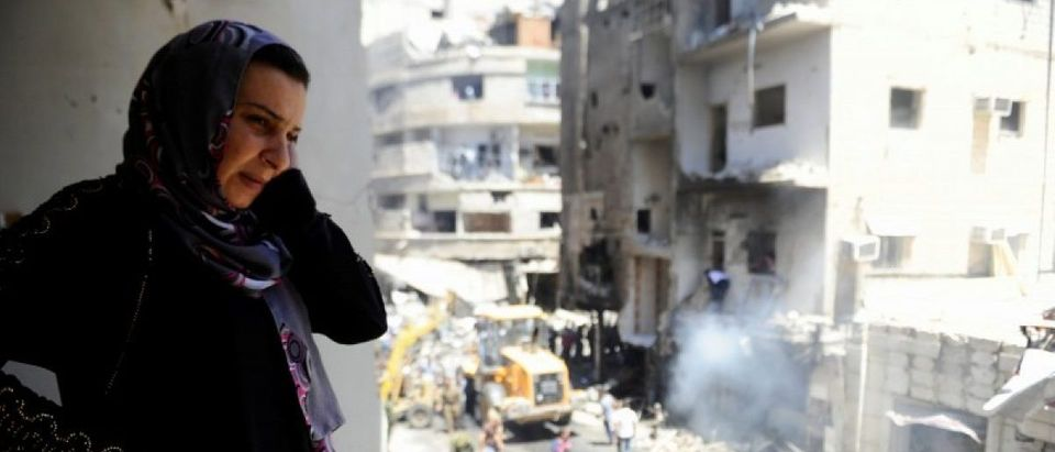 A woman inspects a damaged site after a suicide and car bomb attack in south Damascus Shi'ite suburb of Sayeda Zeinab
