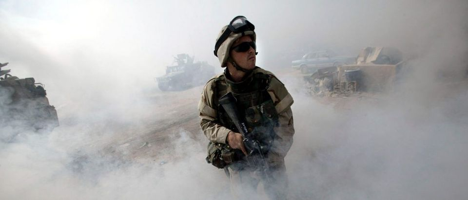 U.S. Army medic stands guard in smoke haze during search operation in Baghdad.