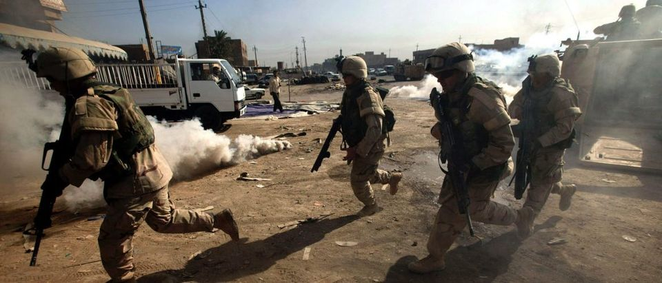 U.S. Army troops run into building during a Baghdad search operation.