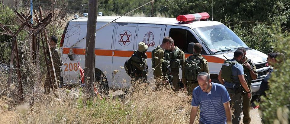 An Israeli ambulance and soldiers are seen outside a house in the Jewish settlement of Kiryat Arba in the occupied West Bank where a 13-year-old Israeli girl was fatally stabbed on June 30 (Getty Images)
