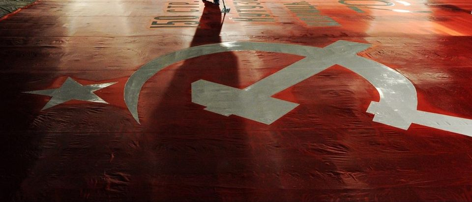 An employee cleans a giant replica of the Soviet Banner of Victory at Saint Petersburg's Lenfilm film studio