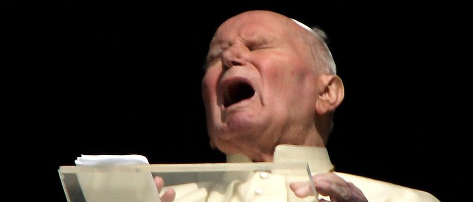 File photograph shows Pope John Paul II grimacing as he appears at the window of his private ...