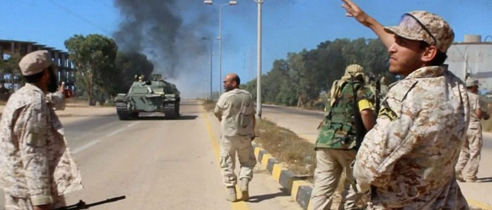 Still image of soldiers from a force aligned with Libya's new unity government walking along a road during an advance on the eastern and southern outskirts of the Islamic State stronghold of Sirte