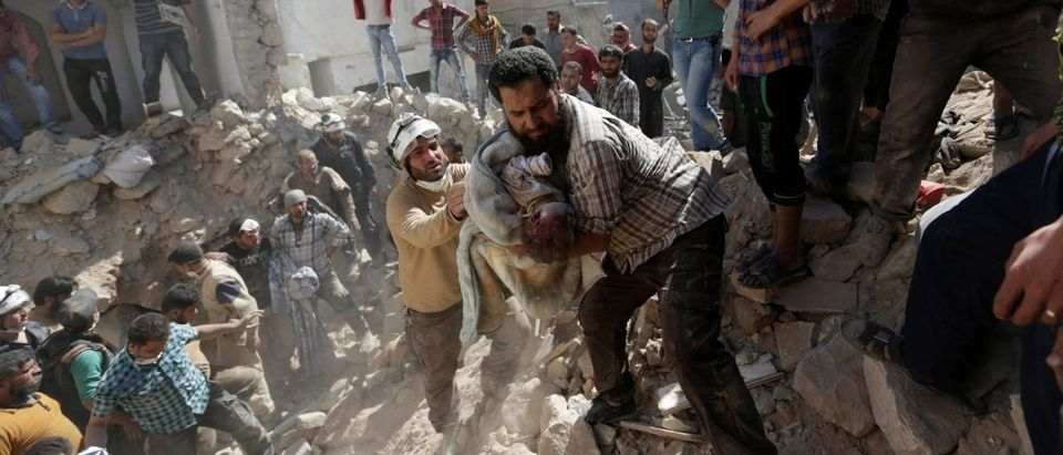 Civil defence members remove the body of a dead child from under the rubble at a site hit by airstrike in the rebel-controlled area of Maaret al-Numan town in Idlib province