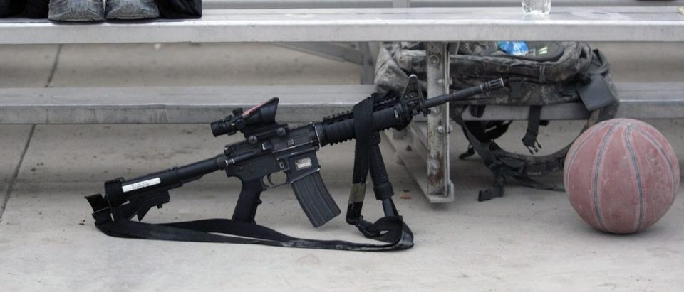 A plastic bottle of water, an AR-15 rifle and an extra basketball lie on a bleacher at Salerno Camp