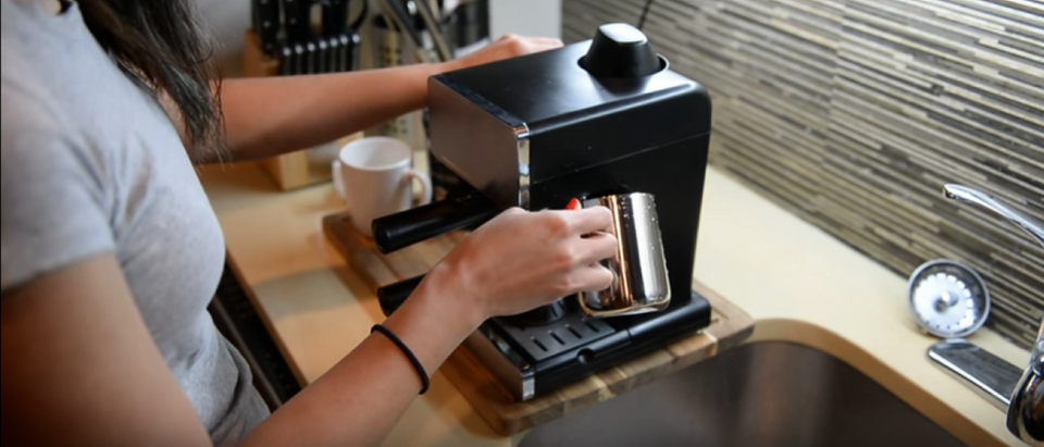 A woman makes an espresso drink with her Mr. Coffee machine
