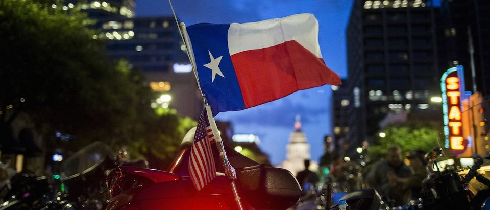 A Texas state flag attached to a bike waves after the Republic of Texas (ROT) Biker Rally bike parade in Austin, Texas