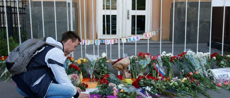 A man places a candle for the victims of the shooting at a gay nightclub in Orlando in front of the U.S. Embassy in Moscow